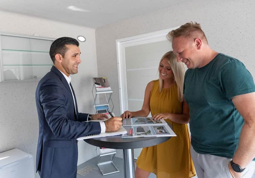Ein Paar wird von einem Berater professionell zu Fenstern und Sonnenschutz beraten
