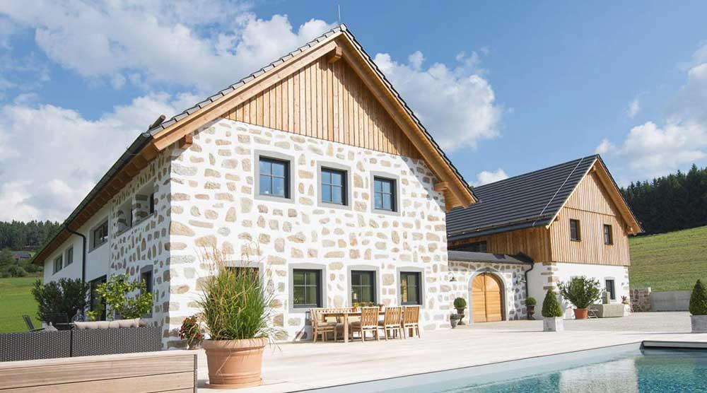 Ein Bauernhof, der in ein Haus mit Steinmauern, klassischen Fenstern und einem Swimmingpool im Garten umgewandelt wurde