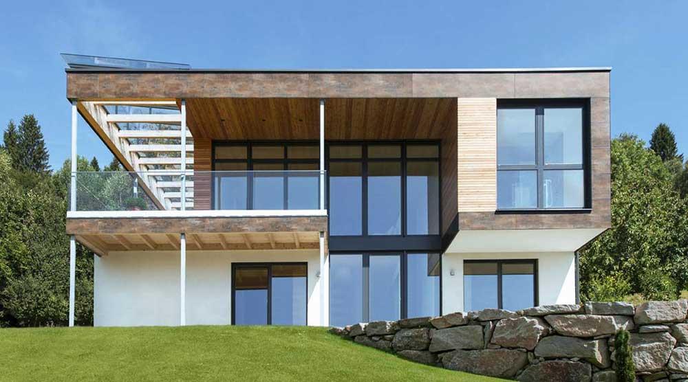 Ein modernes Haus in Holz und Weiß mit großen Fenstern