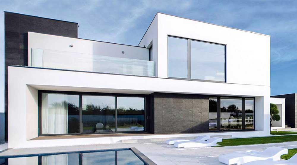 Ein modernes Haus in Weiß mit großen Fenstern und einem Swimmingpool im hinteren Garten