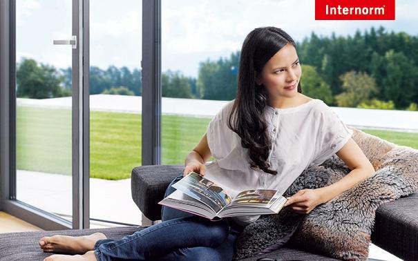 Frau liest Zeitung und genießt den Blick durch das Fenster