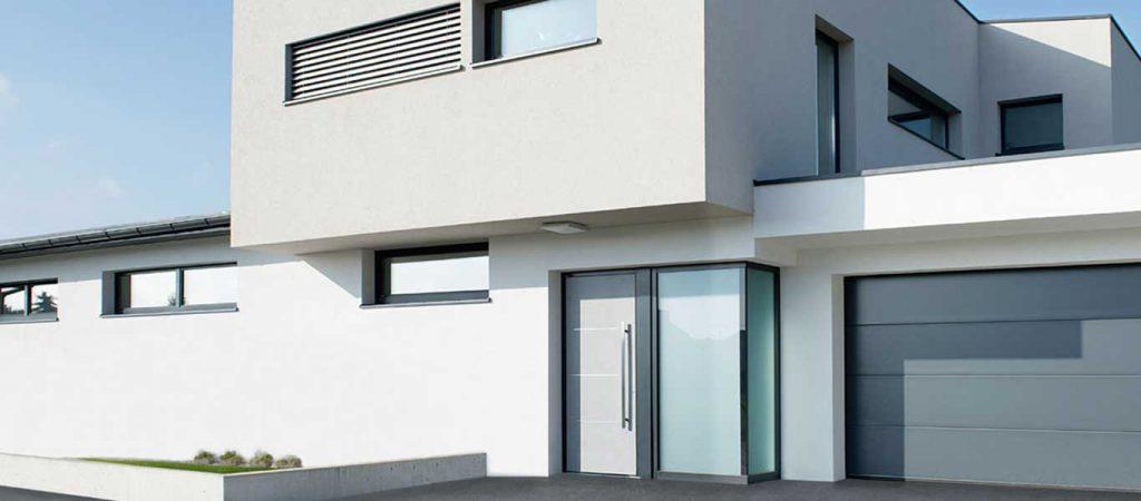 Ein weißes modernes Haus mit einer Aluminium-Eingangstür und einem Garagentor